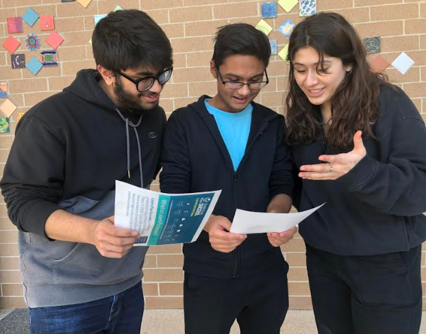 Umar Khan (Adv. 101), Sadrish Acharya (Adv. 101), and Julia Torres (Adv. 103) pore over material from college night. Photo by Kate Clemenz.