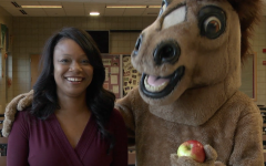 Principal Mest with school mascot Marty the Mustang in the cafeteria.
