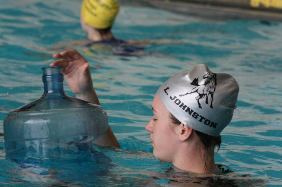 Senior Luna Johnston (Adv. 108) swimming with a filled water jug to work on treading during practice